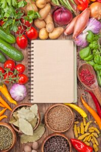 Assortment of fresh vegetables and blank recipe book on a wooden background