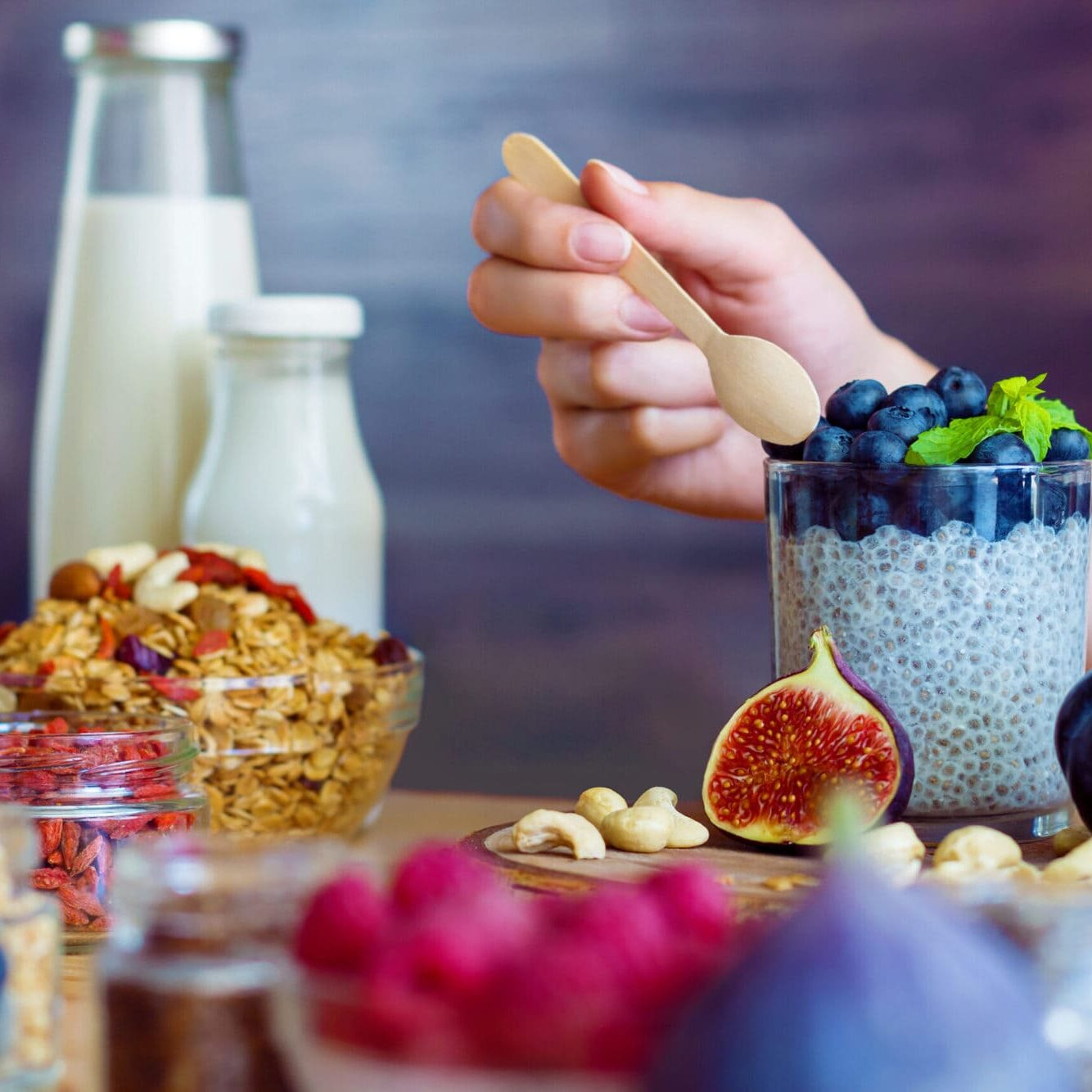 Closeup female hands are preparing organic yogurt with chia for good digestion, functioning of gastrointestinal tract. Summer berries, nuts, fruits, dairy products on table. Healthy food concept.
